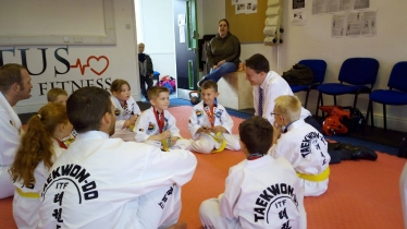 Young participants showing Simon their medals